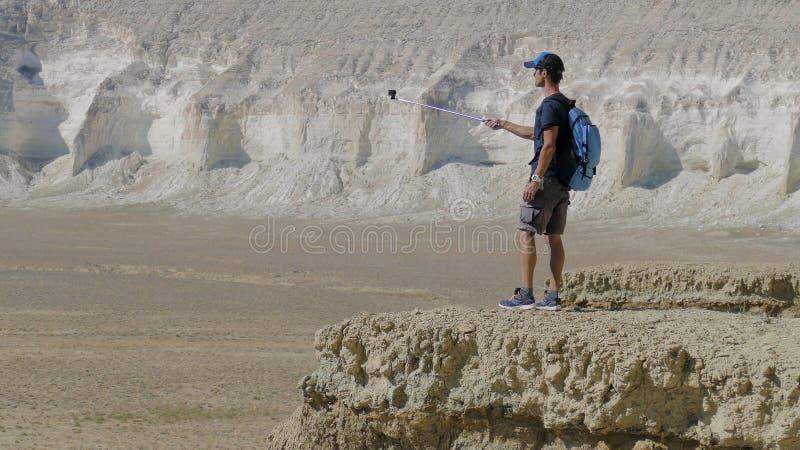 En ung handelsresande står på kanten av en klippa och gör en selfie royaltyfria foton