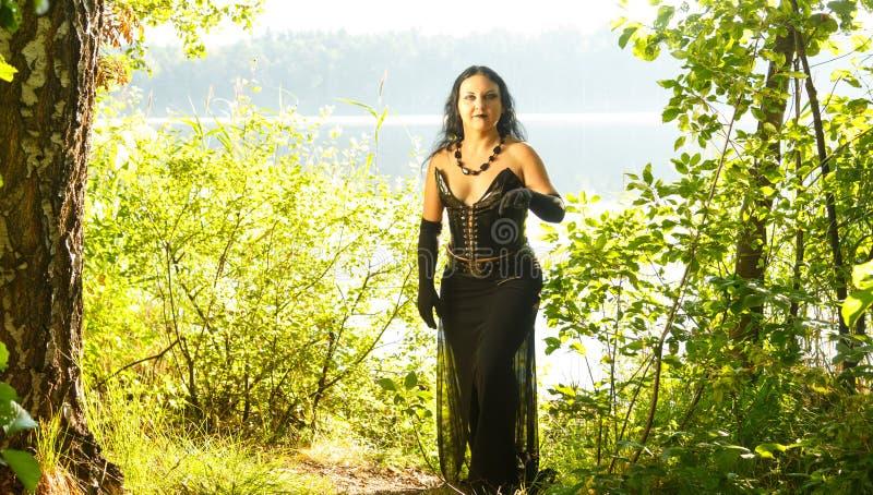 En ung kvinna är en trollkvinna i svart vid sjön halloween royaltyfri fotografi