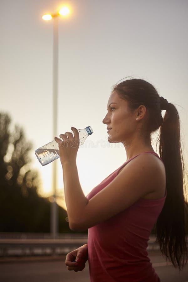 En ung kvinna, 20-29 år, dricksvatten från en flaska fotografering för bildbyråer