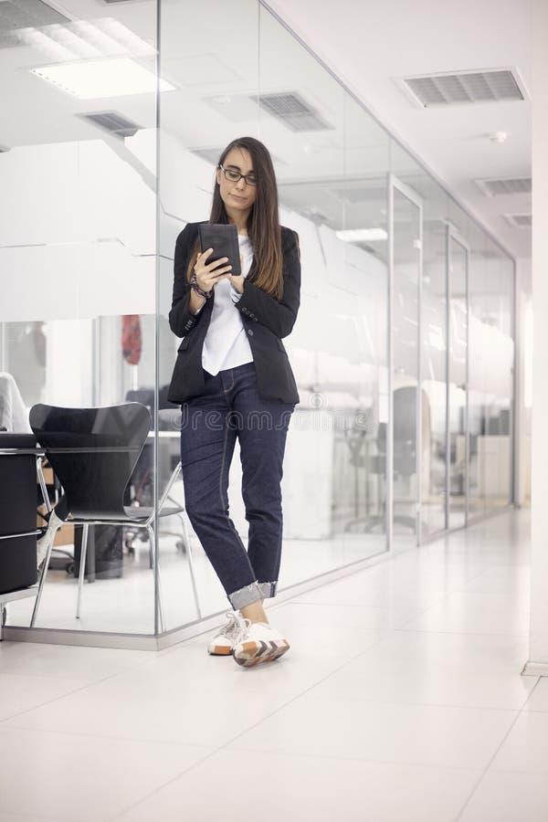 En ung kvinna, arbetare för vit krage och att stå tycka om hennes arbete, genom att använda minnestavlan full längd som skjutas,  royaltyfri fotografi