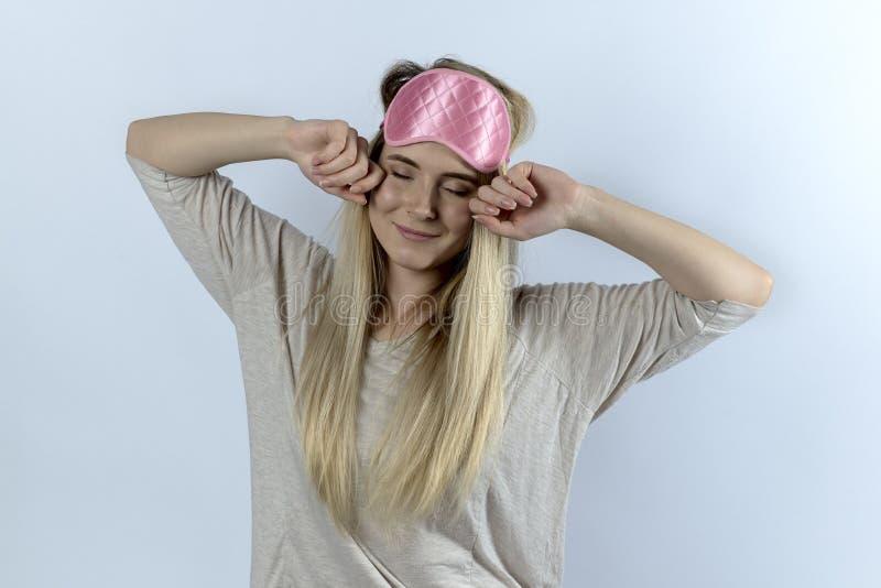 En ung kvinna eller en student i pyjamas och en ögonbindel gäspar och royaltyfri bild