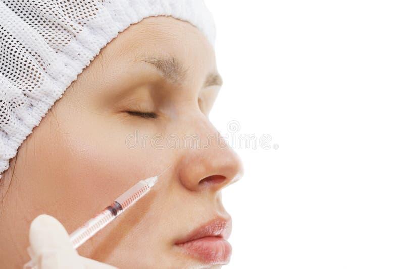 En ung kvinna får en injektion av Botox En kvinna i en skönhetsalong Plastikkirurgiklinik royaltyfria foton