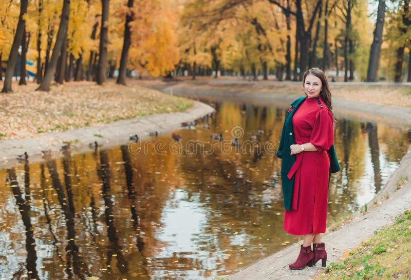 En ung kvinna går i hösten parkerar Brunettkvinna som bär ett grönt lag och en röd klänning fotografering för bildbyråer