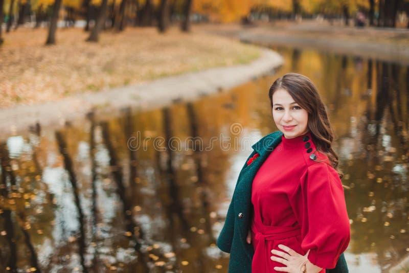 En ung kvinna går i hösten parkerar Brunettkvinna som bär ett grönt lag och en röd klänning arkivfoton