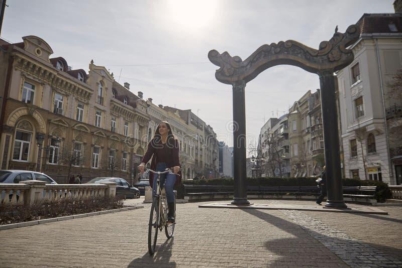 En ung kvinna, 20-29 gamla som år rider en retro gammal cykel på en europeisk fyrkant för gammal stad Le som ?r lyckligt royaltyfria foton