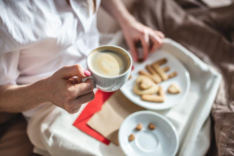 En ung kvinna har en romantisk frukost på morgonen. Kaffe och ordkärlek från cookies Överraska på Alla hjärtans dag royaltyfria foton