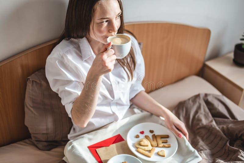En ung kvinna har en romantisk frukost på morgonen. Kaffe och ordkärlek från cookies Överraska på Alla hjärtans dag royaltyfri foto