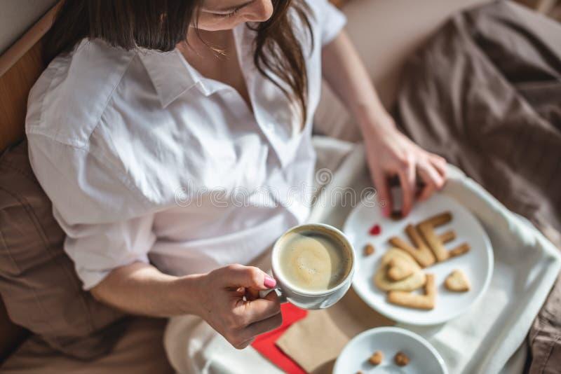 En ung kvinna har en romantisk frukost på morgonen. Kaffe och ordkärlek från cookies Överraska på Alla hjärtans dag arkivbilder