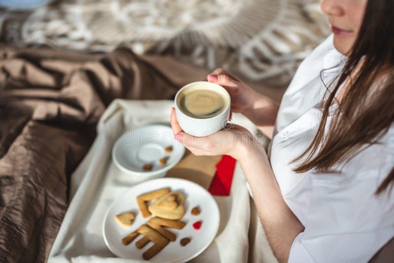 En ung kvinna har en romantisk frukost på morgonen. Kaffe och ordkärlek från cookies Överraska på Alla hjärtans dag royaltyfri bild