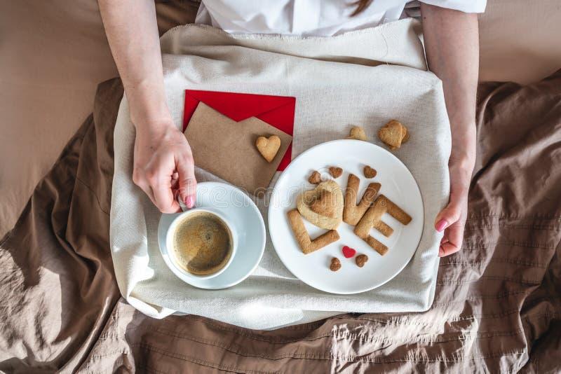 En ung kvinna har en romantisk frukost på morgonen. Kaffe och ordkärlek från cookies Överraska på Alla hjärtans dag arkivfoton