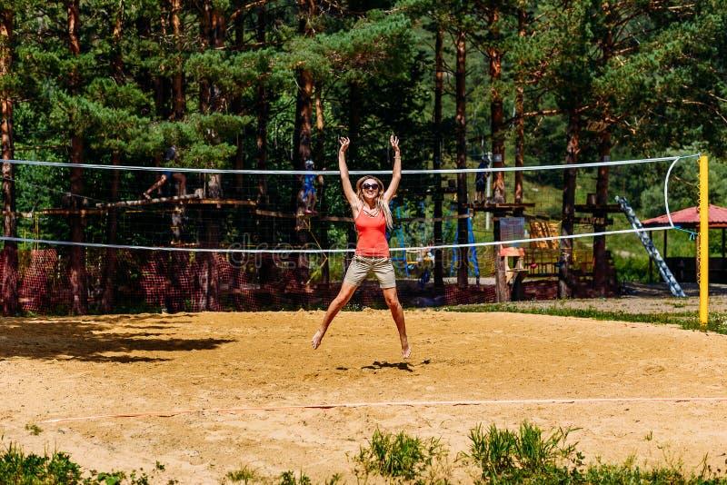 En ung kvinna hoppar på volleybollfältet på stranden arkivfoto