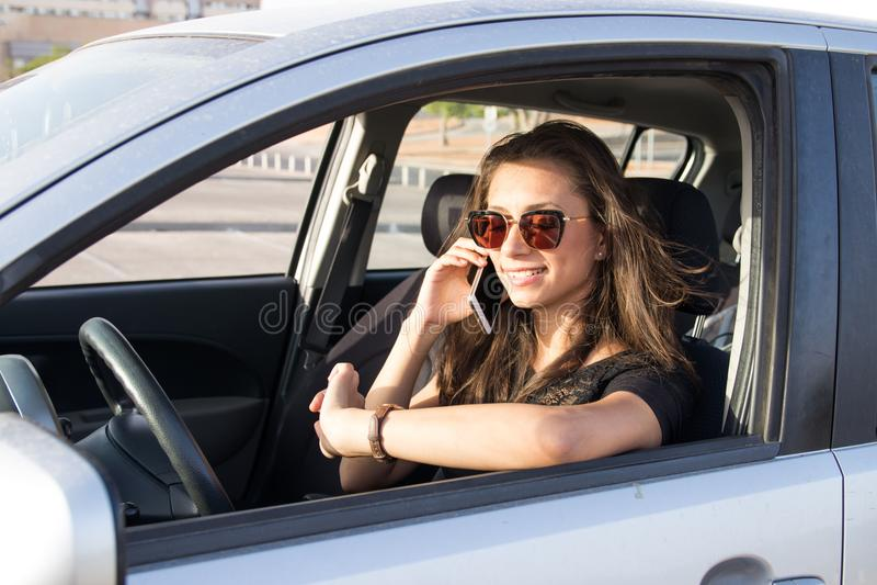 En ung kvinna i bilsamtalen på den smarta telefonen och dreven arkivbild