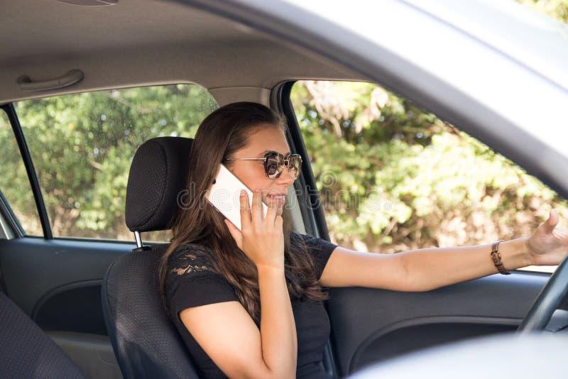 En ung kvinna i bilsamtalen på den smarta telefonen och dreven royaltyfri foto