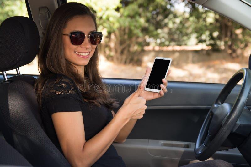 En ung kvinna i carhhållen en smart telefon med tummar upp royaltyfri bild