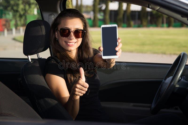 En ung kvinna i carhhållen en smart telefon med tummar upp arkivbild