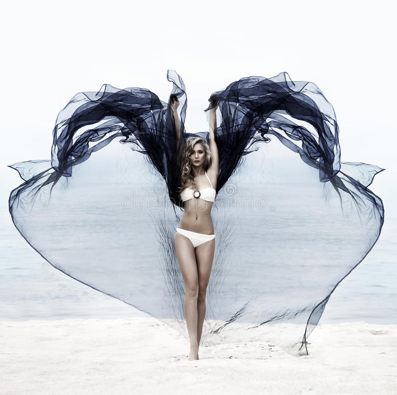 En ung kvinna i en baddräkt på stranden arkivbilder