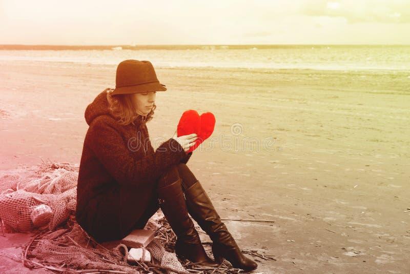 En ung kvinna i en hatt och ett lag sitter på kusten av fjärden på ett fisknät med en flott hjärta i hennes händer, den ljusa ton royaltyfria bilder