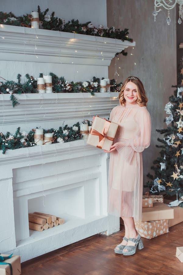 En ung kvinna i ett rosa klänninganseende vid spisen på bakgrunden av en julgran royaltyfri foto