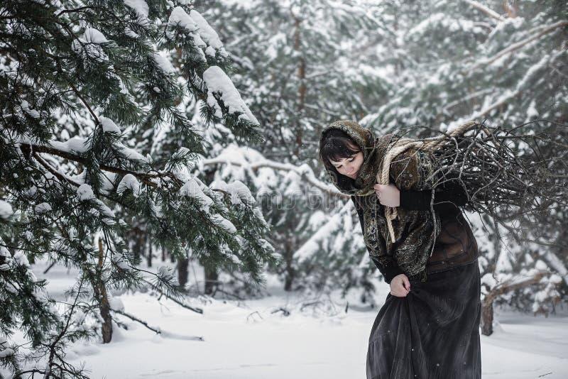 En ung kvinna i gammal kläder står med småskog i ett vinterskogtecken från sagan arkivfoto
