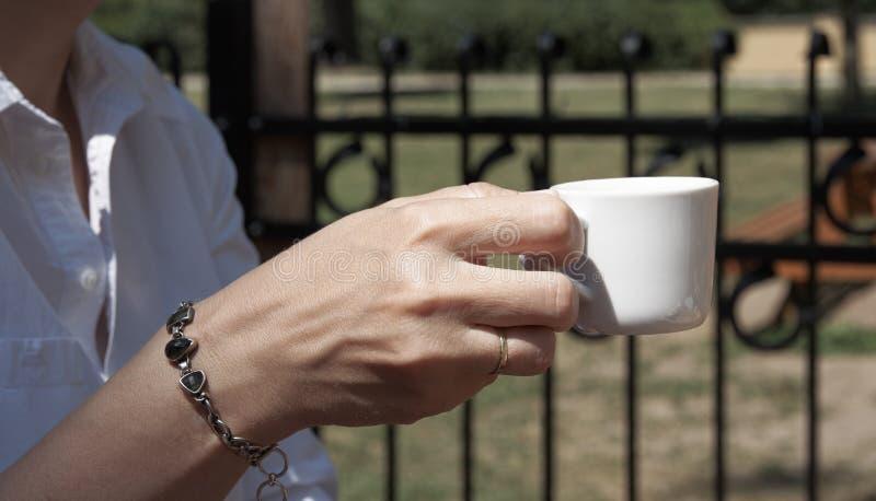 En ung kvinna i en trädgårds- restaurang rymmer ett kaffe i handen, intelligens royaltyfri bild
