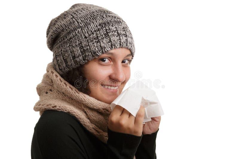 En ung kvinna i vintertid med sjukdomen måste nysa och blåsa in i en näsduk som isoleras på vit bakgrund arkivbild