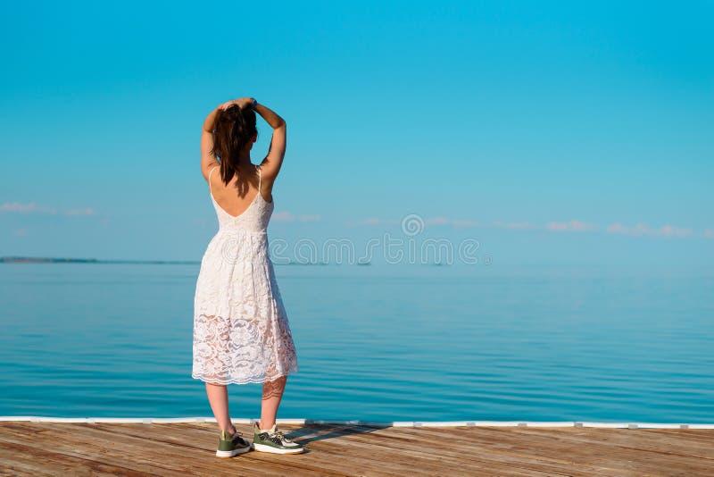 En ung kvinna i en vit klänning står på en träpir med hennes händer på hennes huvud som ser in i avståndet fotografering för bildbyråer
