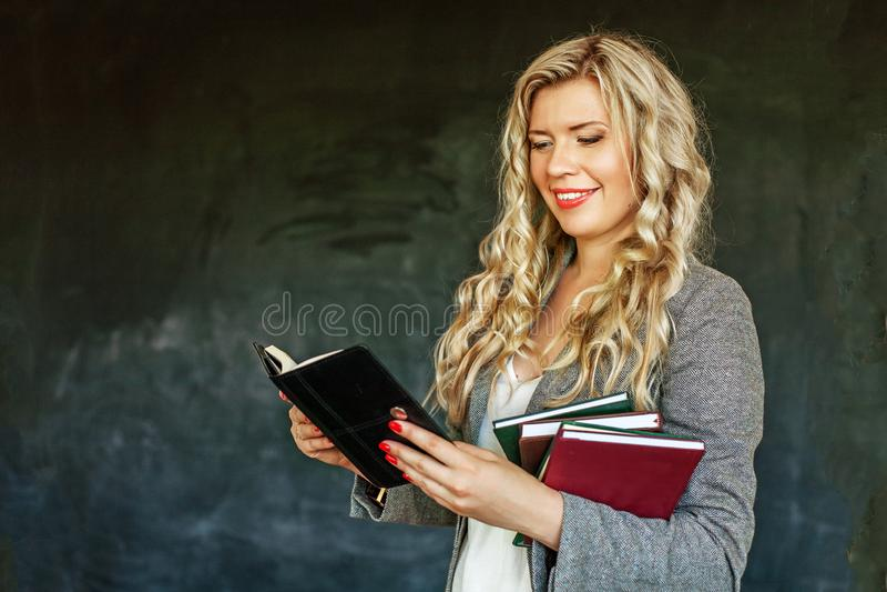 En ung kvinna läser och rymmer många böcker Begreppet av learnin royaltyfri fotografi