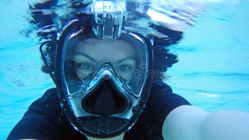 En ung kvinna med en dyka maskering som snorklar i havet arkivfoto