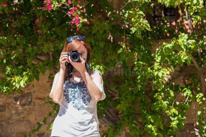 En ung kvinna med rödaktigt hår tar fotografier med hennes kamera bredvid en vägg som täckas med bougainvillean Caceres royaltyfri foto