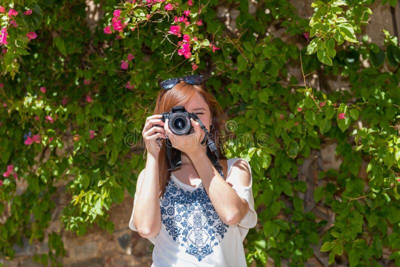 En ung kvinna med rödaktigt hår tar fotografier med hennes kamera bredvid en vägg som täckas med bougainvillean Caceres arkivbilder
