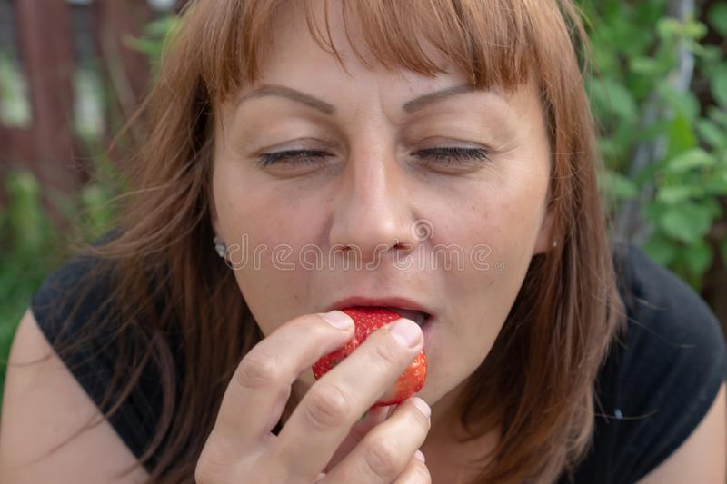 En ung kvinna med rött hår biter mogna jordgubbar och stänger hennes ögon med nöje royaltyfri bild