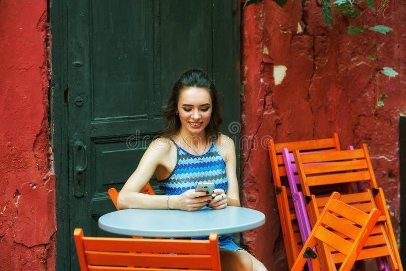 En ung kvinna med en telefon i henne händer arkivbild