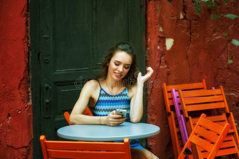 En ung kvinna med en telefon i henne händer royaltyfria bilder