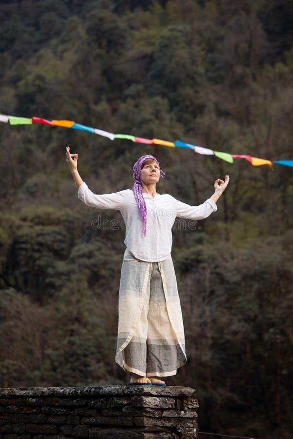 En ung kvinna mediterar på bakgrunden av nepalesiska böner nepal Bergen fotografering för bildbyråer