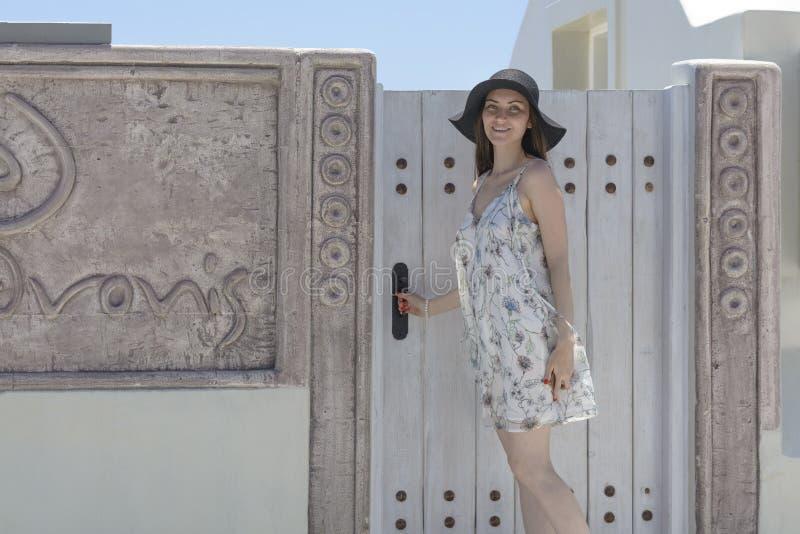 En ung kvinna nära dörren till lägenheten på ön av Santorini royaltyfri bild