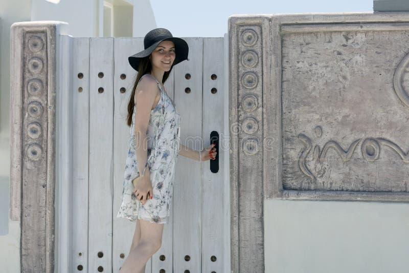 En ung kvinna nära dörren till lägenheten på ön av Santorini royaltyfri fotografi