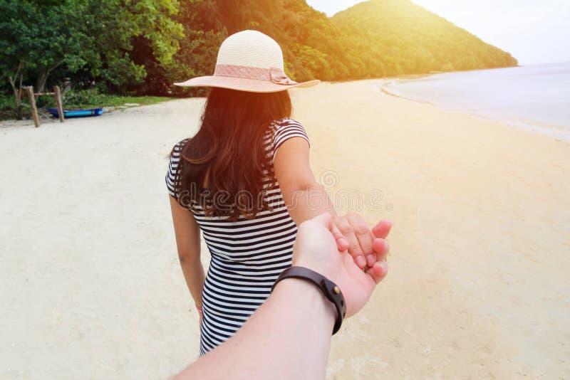 En ung kvinna på en strand rymmer en hand för man` s royaltyfri foto