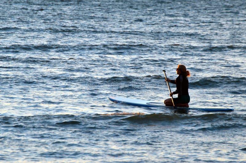 En ung kvinna paddlar in i det öppna havet fotografering för bildbyråer