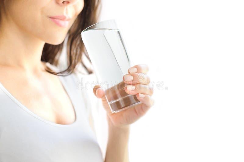 En ung kvinna rymmer ett exponeringsglas av vatten i hennes hand och ska just att dricka den Vit bakgrund kopiera avstånd royaltyfri foto