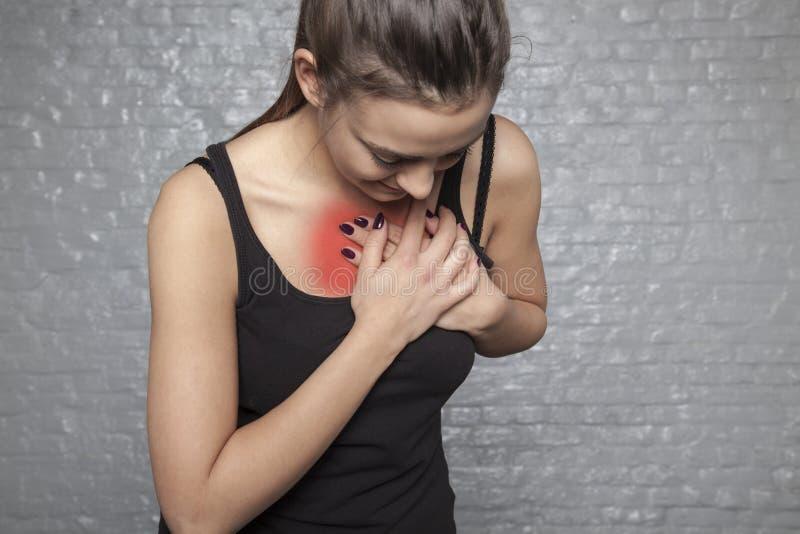 En ung kvinna rymmer hennes bröstkorg, möjlig hjärtinfarkt, först royaltyfria bilder