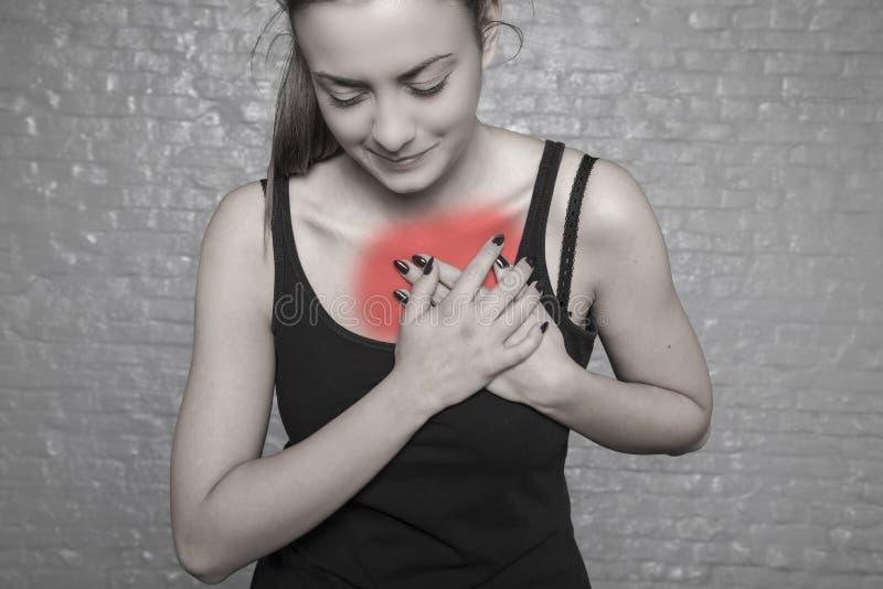 En ung kvinna rymmer hennes bröstkorg, möjlig hjärtinfarkt, först arkivfoton