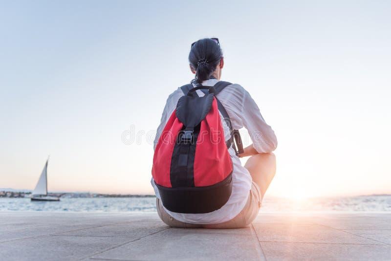 En ung kvinna sitter avkopplat och ser solnedgången på kusten royaltyfria bilder