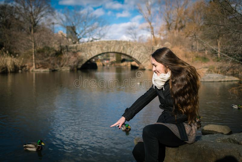 En ung kvinna sitter i Centralet Park av New York och ser tidigt på morgonen på sjön En person arkivbilder
