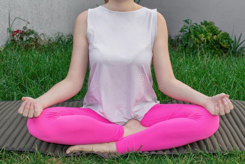 En ung kvinna sitter i en lotusblommaposition, öva yoga på en yoga som är matt på gräset Närbild kroppsdelar royaltyfri foto