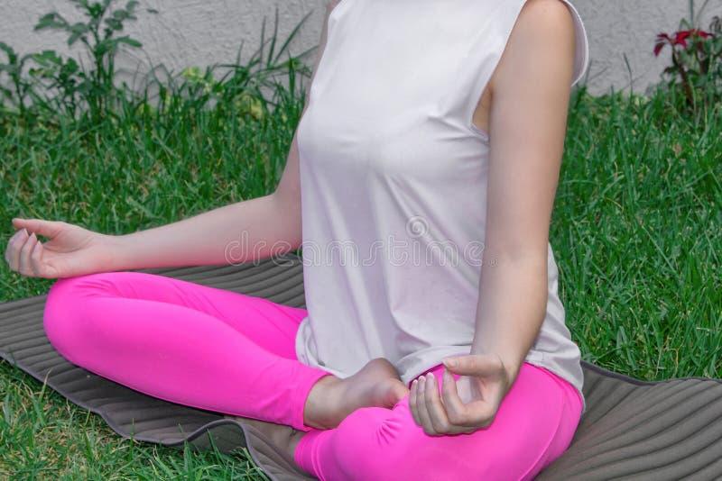 En ung kvinna sitter i en lotusblommaposition, öva yoga på en yoga som är matt på gräset Närbild kroppsdelar arkivfoton
