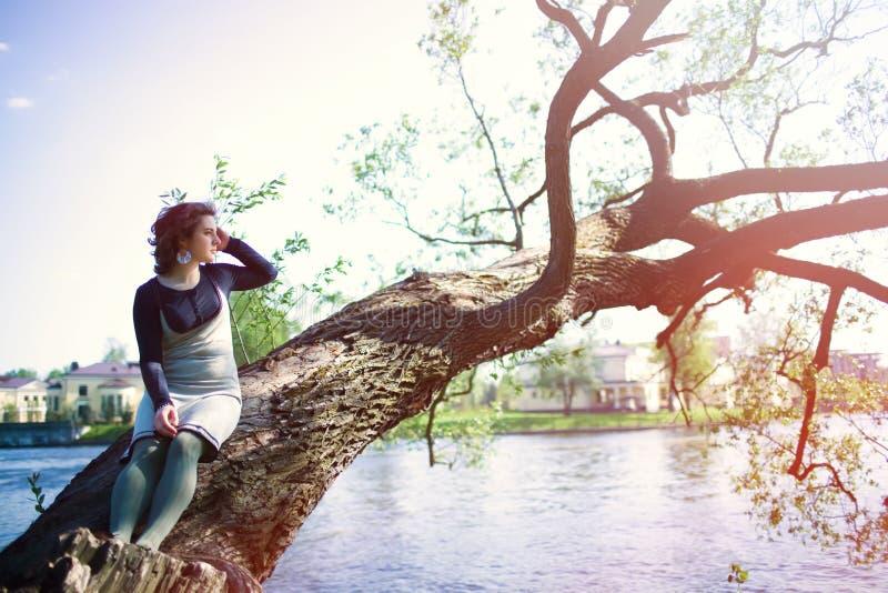 En ung kvinna sitter på en trädfilial nära vattnet och trycker på hennes hår Vårstående på solnedgången royaltyfria bilder