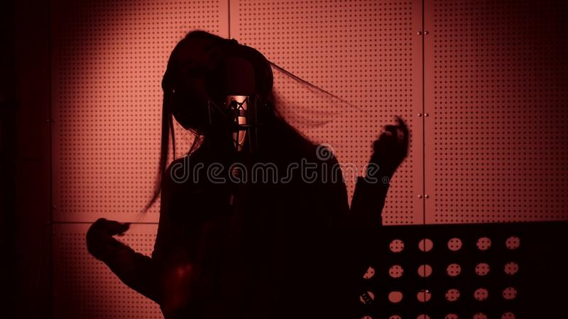 En ung kvinna sjunger en sång i en mikrofon i en inspelningstudio under neonljus royaltyfri fotografi