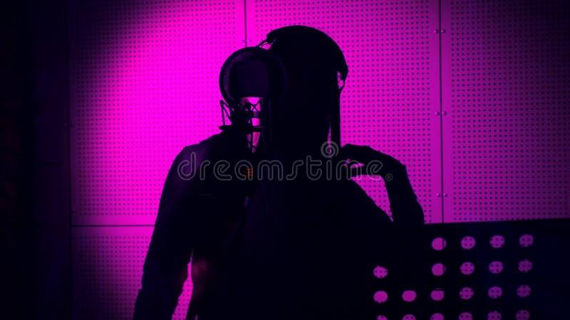 En ung kvinna sjunger en sång i en mikrofon i en inspelningstudio under neonljus arkivfoton
