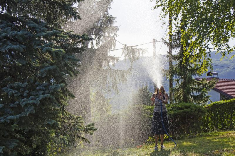 En ung kvinna som bevattnar en gräsmatta i gården av huset, en backgr royaltyfri bild
