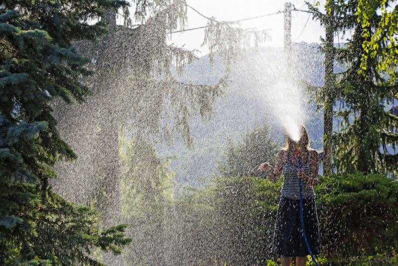 En ung kvinna som bevattnar en gräsmatta i gården av huset, en backgr royaltyfri foto